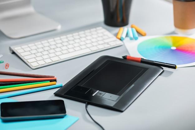 노트북이있는 회색 책상, 빈 시트가있는 메모장, 꽃 냄비, 스타일러스 및 태블릿