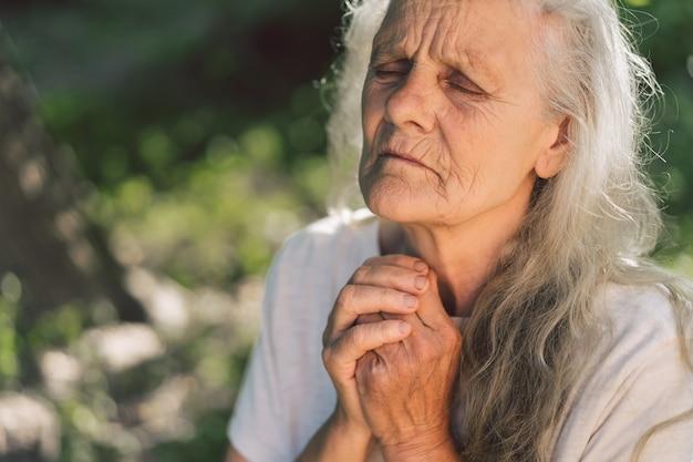 白髪のおばあさんが野外で祈っています。