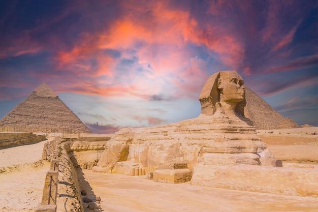 기자의 대 스핑크스와 배경에는 세계에서 가장 오래된 장례식 기념물 인 일몰 기자의 피라미드가 있습니다. 이집트 카이로시에서