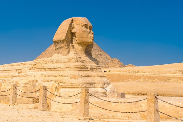 ギザの大スフィンクスとその背景には、ある夏の午後、世界最古の葬儀の記念碑であるギザのピラミッドがあります。エジプト、カイロ市