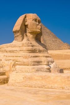 ギザの大スフィンクスとその背景には、世界最古の葬儀の記念碑であるギザのピラミッドがあります。エジプトのカイロ市。縦の写真