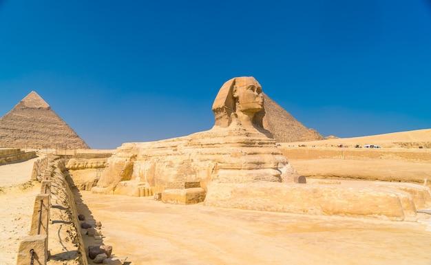 ギザの大スフィンクスとその背景には、世界最古の葬儀の記念碑であるギザのピラミッドがあります。エジプト、カイロ市