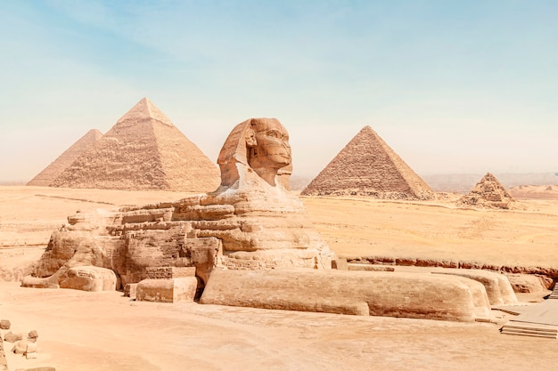 ライオンの体とファラオの顔をした大きなスフィンクスは、明るい晴れた空の下で、ギザのすべての有名なピラミッドを背景に砂の上に横たわっています。カイロ、エジプト。