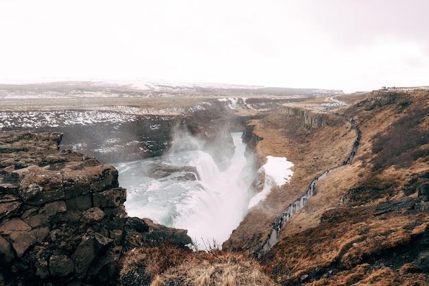 ゴールデンリングの観光客の南アイスランドの大きな滝のグトルフォスは歩道を歩きます