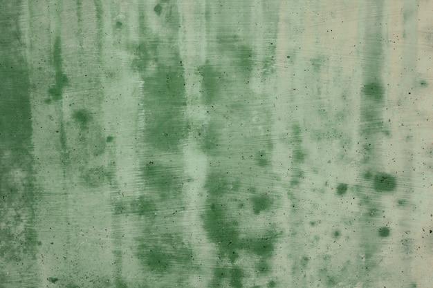 緑のセメント壁が汚れています。