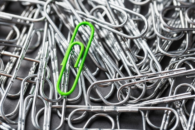 Зеленая канцелярская скрепка выделяется на текстурированном фоне серебряных канцелярских скрепок.