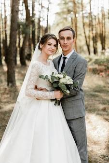 Жених и невеста крепко обнимаются от сильной любви. молодожены гуляют по лесу. прогулка по парку молодоженов. счастливый брак.