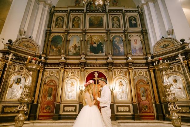화환을 입은 신랑과 신부는 결혼식 중에 교회 제단에서 손을 잡고 서 있습니다.
