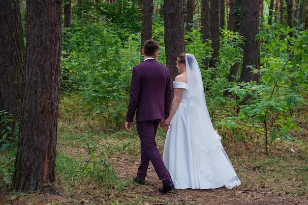 Жених и невеста гуляют по лесу в свадебных платьях