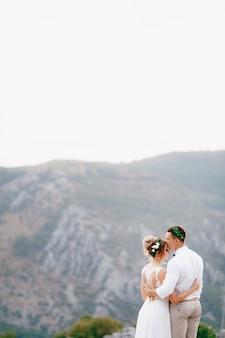 花婿と花輪を持った花嫁が山の頂上に立っています