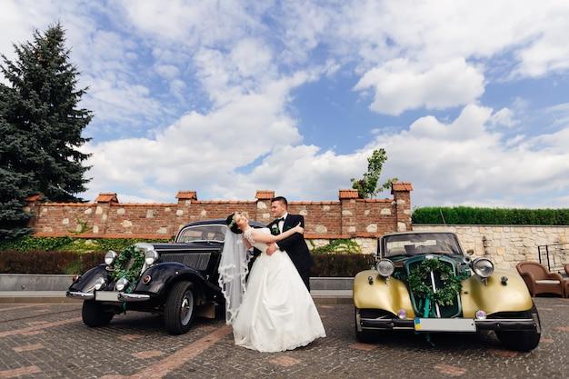 Жених обнимает невесту, а она отгибает две красивые ретро-машины, украшенные венком.