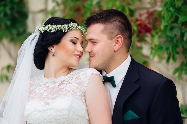 Жених обнимает невесту сзади, молодожены смотрят друг на друга крупным планом