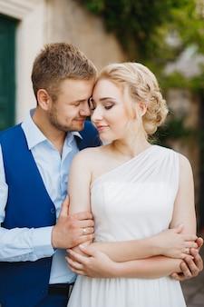 新郎は花嫁を後ろから優しく抱きしめ、花嫁は腕を組んで、カップルは抱きしめます