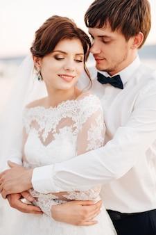 Жених нежно обнимает невесту сзади