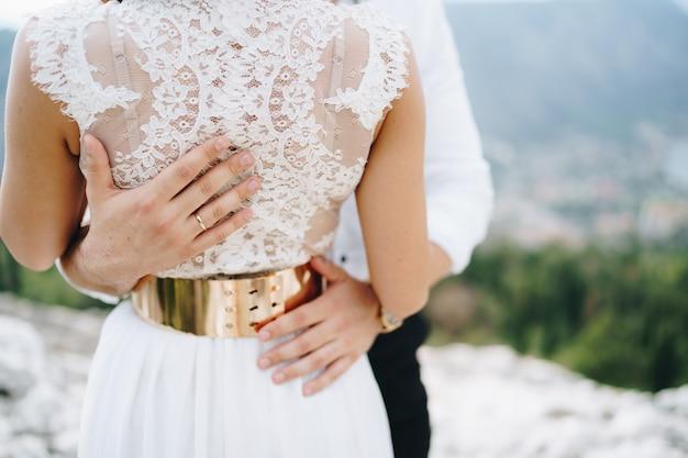 Жених нежно обнимает невесту руками жениха на талии невесты крупным планом