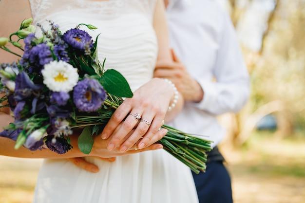 新郎は花嫁をオリーブの木立に優しく抱きしめます花嫁は青い花の花束を持っていますクローズアップ