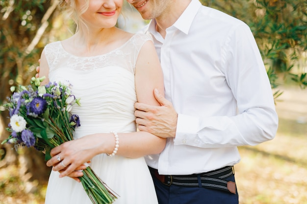 신랑은 신부가 꽃다발을 들고있는 올리브 과수원의 푸른 나무 근처에서 신부를 부드럽게 안아줍니다.