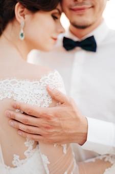 Жених нежно обнимает невесту, положив руку ей на плечо.