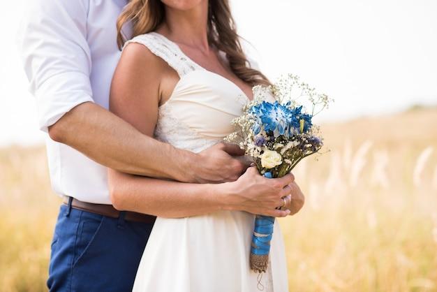 新郎は背景のフィールドに抱き締める花嫁を手渡し、花嫁は結婚式の花束を持っています