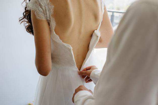 신랑은 신부에게 드레스를 고정시키는 데 도움이됩니다.