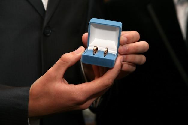 신랑은 금 결혼 반지가있는 상자를 닫습니다.
