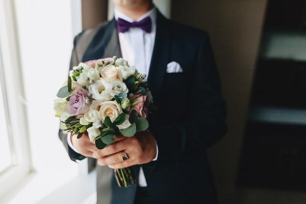 新郎は彼の手で結婚式のブーケを保持しています