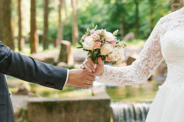 新郎は花嫁にウェディングブーケを差し出します。新婚の手のクローズアップと繊細な花束