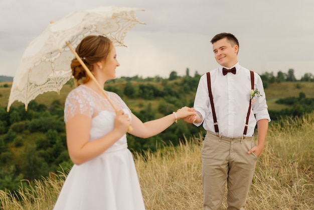 新郎は美しい風景に対して結婚式で手で花嫁を保持します