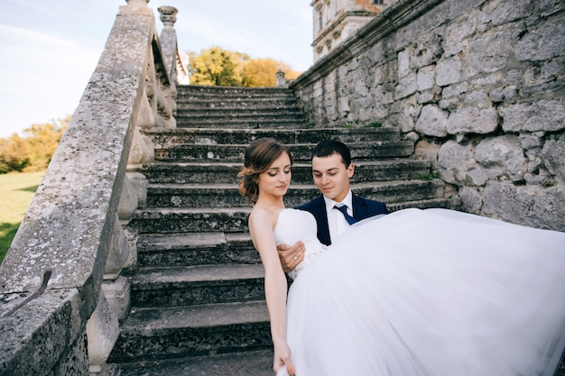 Жених держит невесту на руках. день свадьбы