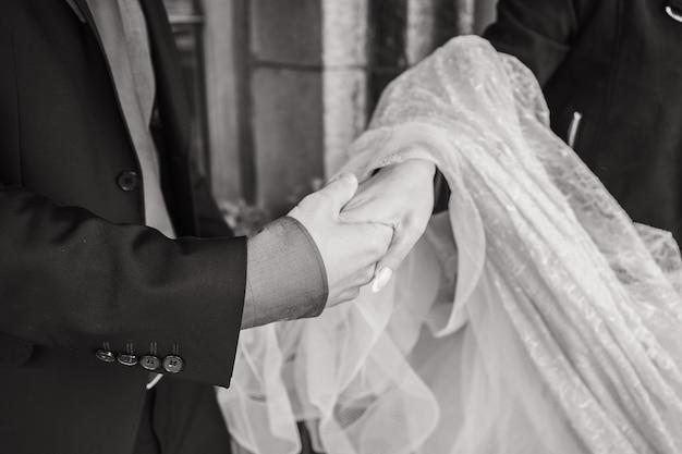 Жених держит руки невесты крупным планом за руки парня, а девушка поддерживает между мужчиной и ...