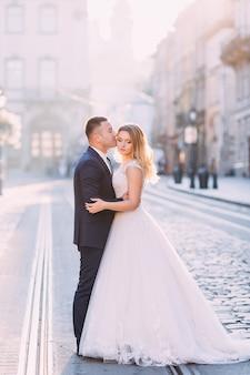 新郎は白いドレスを着て美しい花嫁を抱きしめ、キスします。街の広場にいる新婚夫婦。