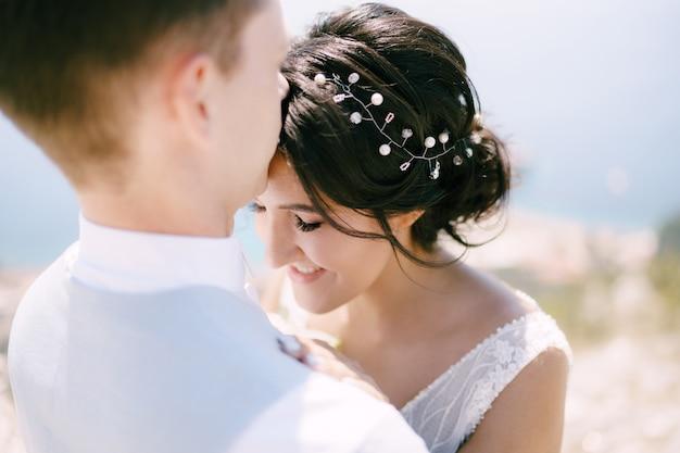 新郎は花嫁を抱きしめ、額にキスをします花嫁の笑顔のクローズアップ