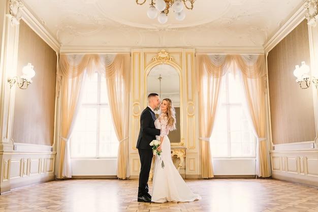 신랑은 신부를 껴안고 눈을 감고 웨딩 부케를 들고 있습니다. 대형 창문과 거울이있는 넓은 객실입니다.