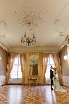 新郎は花嫁を抱きしめ、目を閉じてウェディングブーケを持っています。大きな窓と鏡のある広々としたお部屋です。