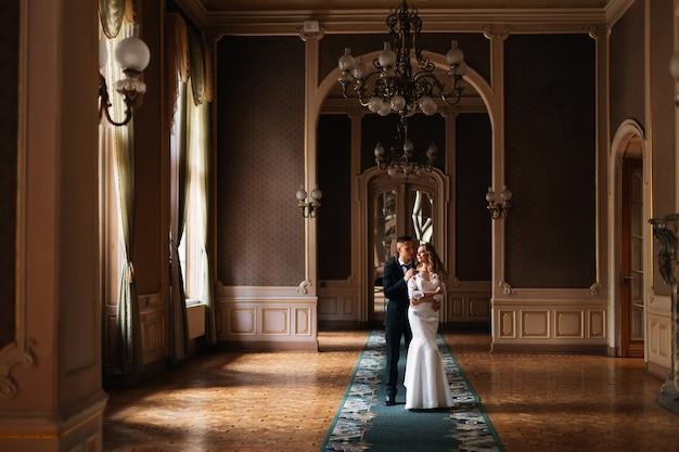 Жених обнимает невесту, и она смотрит в окно. элегантный просторный номер с красивым интерьером и люстрой.