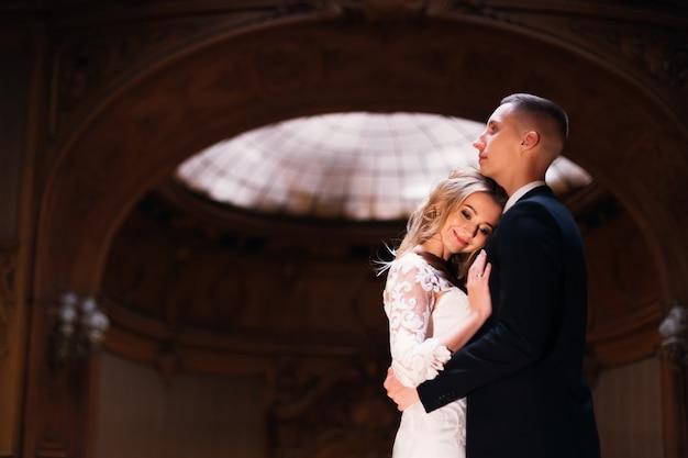 Жених обнимает невесту, а невеста прислоняется к нему и улыбается. молодожены в красивом зале. крупным планом.