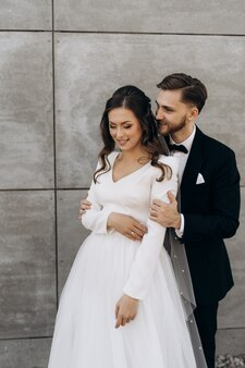 新郎は花嫁を抱きしめ、耳元でささやきます。幸せな結婚式のカップル。新婚。笑顔の花嫁はベール付きの白いウェディングドレスを着ています。黒のスーツを着た新郎
