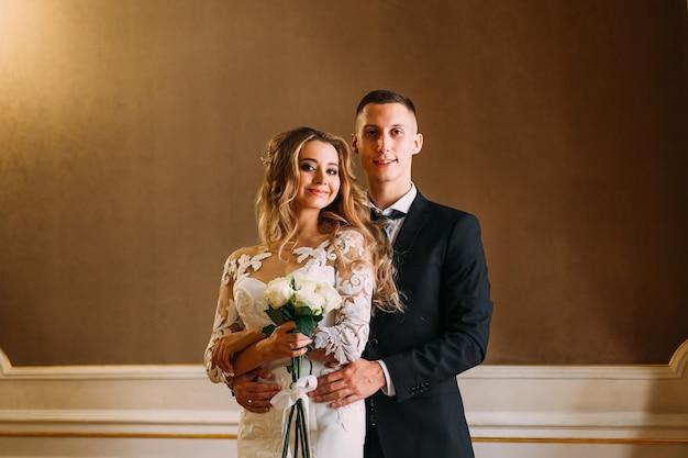 Жених обнимает невесту сзади, а невеста держит свадебный букет.