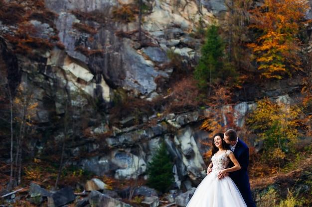 Жених обнимает невесту с обратной стороны, и они улыбаются.