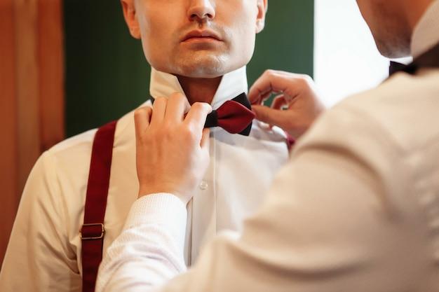 黒のスーツの新郎が蝶を修正します。手と首の拡大図。ウェディングドレス
