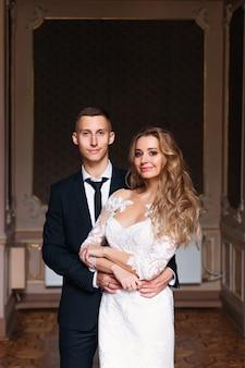 Жених в черном костюме с галстуком обнимает невесту в белом свадебном платье