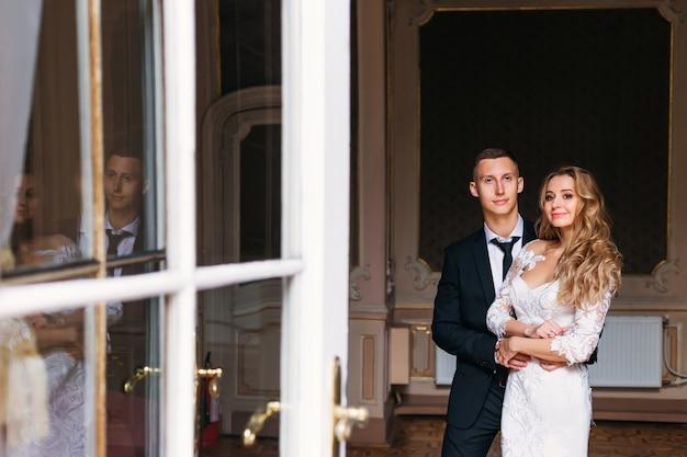 Жених в стильном костюме с галстуком обнимает невесту, интерьер комнаты и двери стеклянными вставками. отражение молодоженов в стекле.