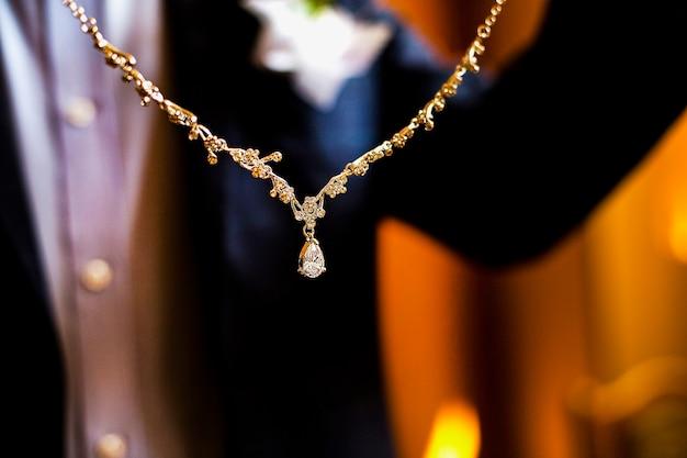 Жених в костюме дарит невесте колье с бриллиантами.