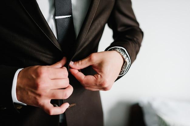 スーツ、シャツ、ネクタイの新郎は白い背景の上に立っています。男はボタンを閉じます。