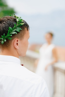 Жених в оливковом венке и белой рубашке перед силуэтом невесты