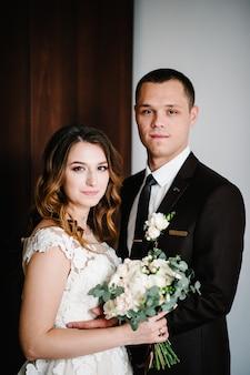 スーツを着た新郎は白いドレスを着た花嫁を抱きしめ、美しいウェディングブーケの花、緑を持ち、自宅でリボンで飾られています。美しい若いカップルの肖像画。