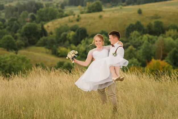新郎は彼の腕の中で美しい花嫁を旋回しています、幸せな新郎は彼の腕の中で美しい風景に対して彼の美しい花嫁を保持しています。結婚式の日。