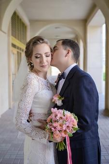 Жених нежно обнимает и целует прекрасную невесту со свадебным букетом в арочной галерее.