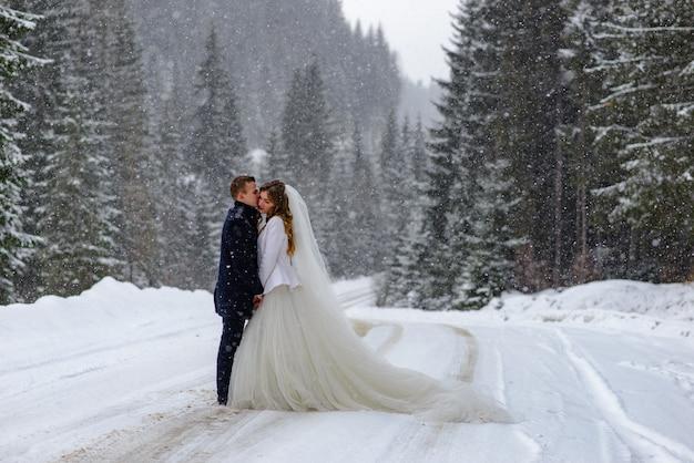 Жених целует невесту на фоне снежного елового леса. идет снег. зимняя свадьба.