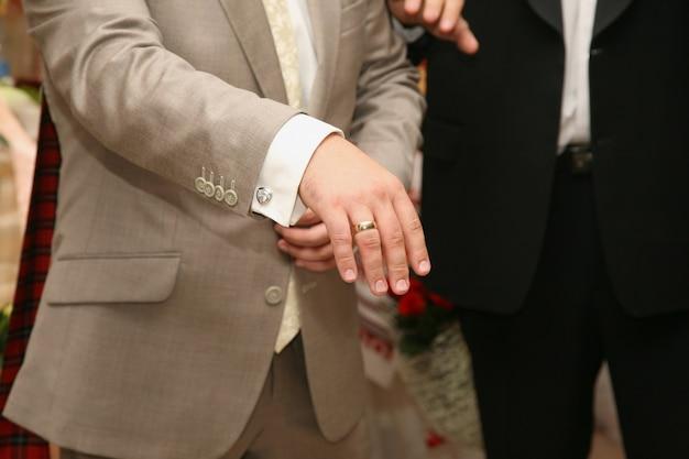 新郎は彼の手に結婚指輪を示しています